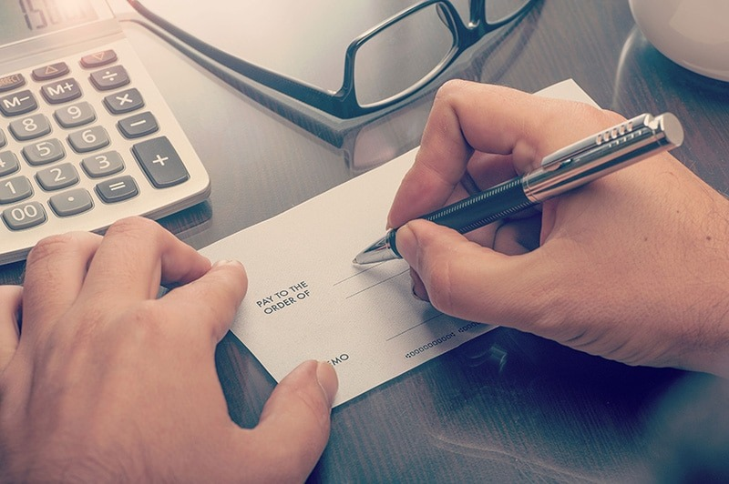 How Claim Payment Works for Home Insurance someone writing a check