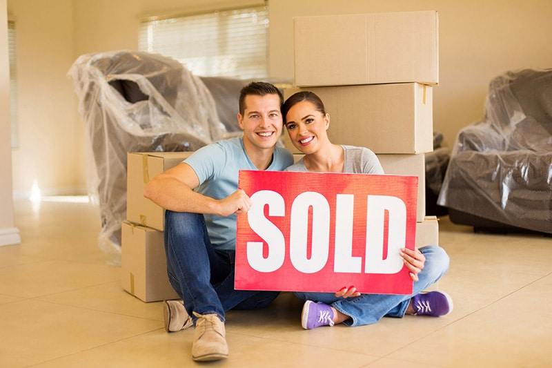 couple holding a sold sign
