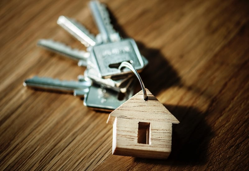 What's the Difference Between Homeowners Insurance and a Home Warranty? house keys with a wooden home statue attached