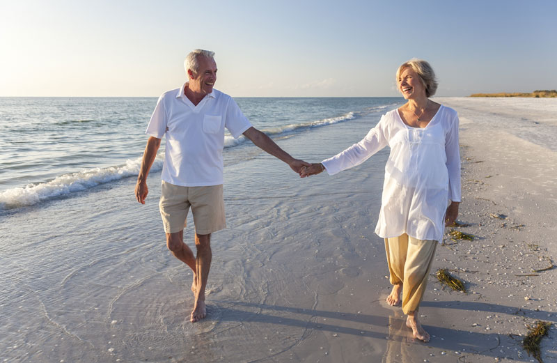 two people holding hands on beach