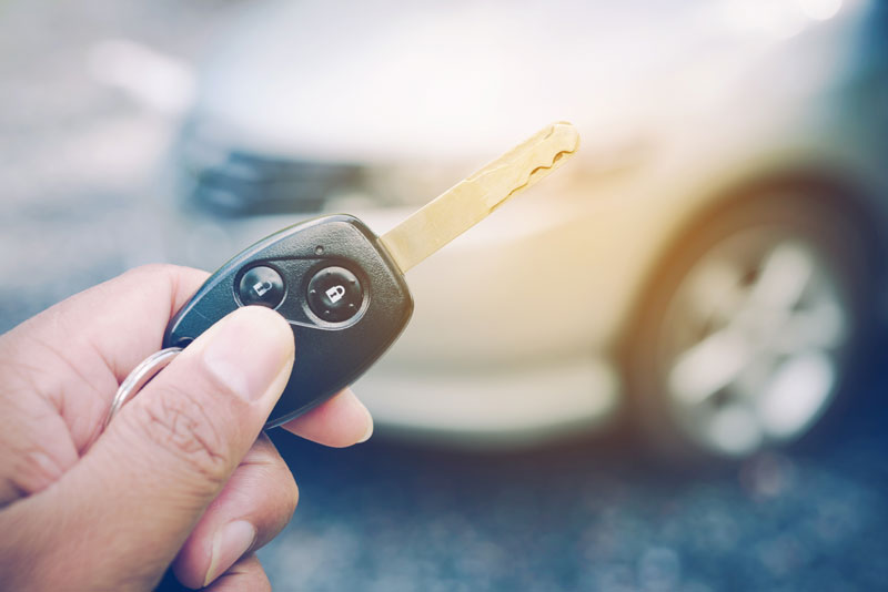 a person holding a vehicle key